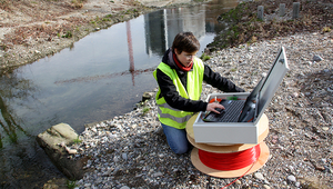 Anne-Marie Kurth at the field site on the restored Chriesbach stream (Canton Zurich): in the method developed by the Eawag researcher, a fibre-optic cable buried in the streambed is used for temperature measurement. (Foto: Andri Bryner)