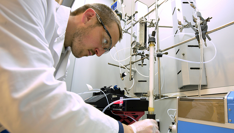 Fig. 1: In the laboratory, scientist Tony Merle tests the novel membrane-based process for ozonation of bromide-containing water: ozone gas fed into a glass reactor diffuses into the water through PTFE membranes. Photo: Andres Jordi, Eawag